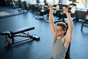 Man shoulder press dumbbells